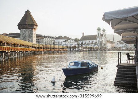 LUCERNE, SWITZERLAND - SEPTEMBER 20, 2014: View of the famous bridge Kapellbruecke (wooden chapel) in the evening in Lucerne. Lucerne is a famous tourist destination in Switzerland.