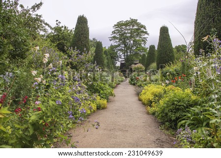 Lucious english garden with colorful flowers - stock photo