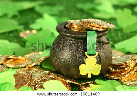 Luck of the Irish: A pot of Gold sits amongst the shamrocks as a symbol of fortune and luck. - stock photo