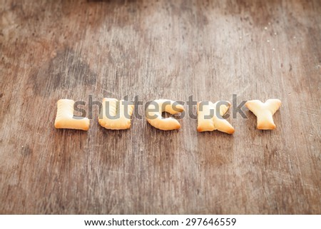 Lucky alphabet biscuit on wooden table, stock photo - stock photo