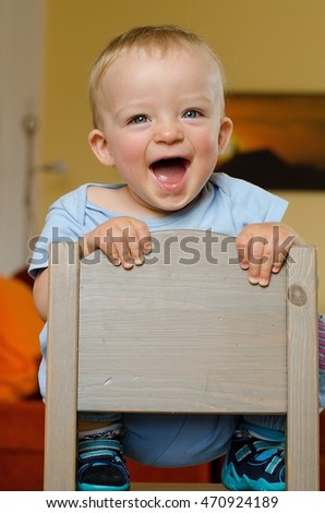 Lucky boy  holding little wooden chair. Toddler climb there and is happy. Child concept.