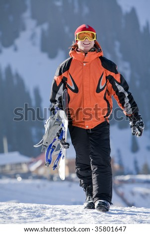 Lucky boy snowboarder in a mountain valley