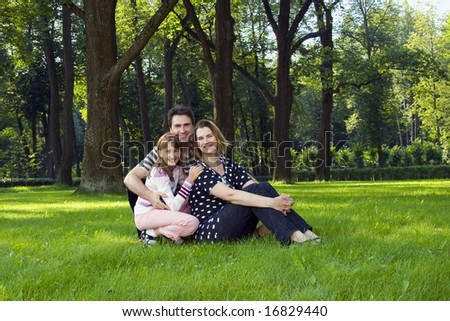 Lucky family on lawn in summer's forest.