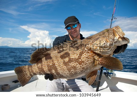 lucky  fisherman holding a big grouper - stock photo
