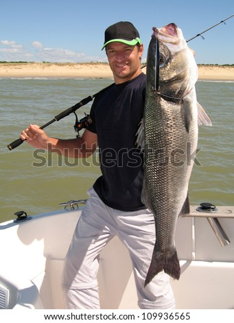 Lucky  fisherman holding a large sea bass - stock photo