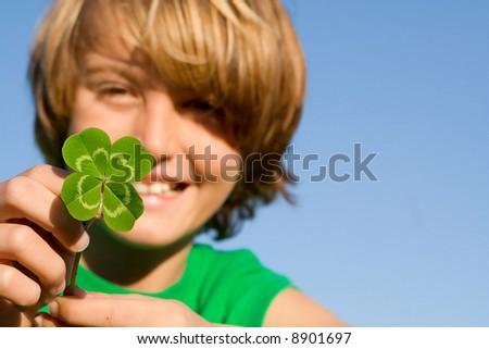 lucky four leaf clover boy FOCUS ON CLOVER. - stock photo