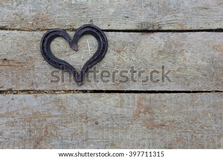lucky horseshoe, used and with rust, on rustic wooden planks, symbol for good luck, background with copy space