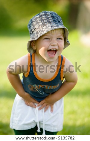 Lucky little boy on garden, summer day - stock photo