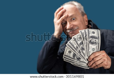 Lucky old man holding with pleasure group of dollar billson blue background with copy-space. Focus on money - stock photo