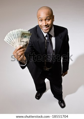 Lucky, wealth businessman excitedly holding group of twenty dollar bills - stock photo
