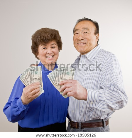 Lucky, wealthy couple excitedly holding group of twenty dollar bills - stock photo