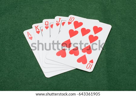 Lucky winning hand of poker cards with a straight royal flush in hearts displayed on a green baize table in a gambling concept