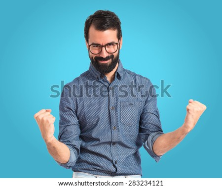 Lucky young hipster man over colorful background