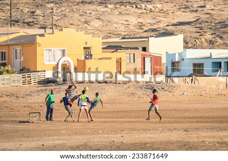 LUDERITZ, NAMIBIA - 24 NOVEMBER 2014: local young people playing football in the playground next to a modern township; for lucky and talented players, soccer is a fast way to escape poverty of slums - stock photo