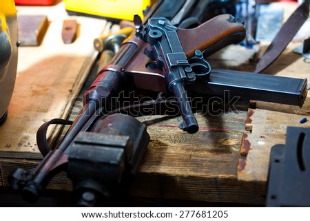Luger pistol and mashinegun MP 38 in gunsmith on old wooden surface - stock photo