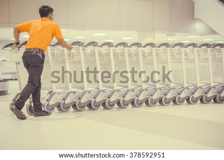 luggage carts at modern airport,trolleys luggage in a row in airport, retro filter effect,selective focus - stock photo