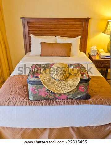 luggage in the beds of a hotel room - stock photo