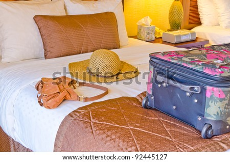 luggage on the bed of a hotel room - stock photo