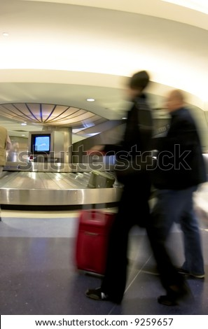 Luggage pick up area in busy airport, with motion-blurred people rushing in the foreground - stock photo