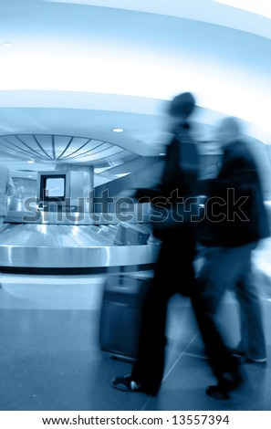 Luggage pick up area in busy airport, with motion-blurred people rushing in the foreground. Blue duotone