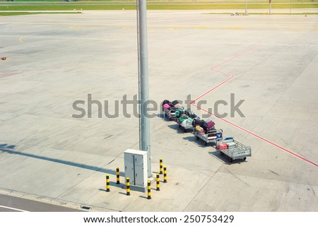 Luggage traffic on an electromobile to the plane. Freight trolleys with loaded baggage on the runway tarmac - stock photo
