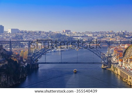 Luis I bridge and small ship sailing the river in Porto, Portugal