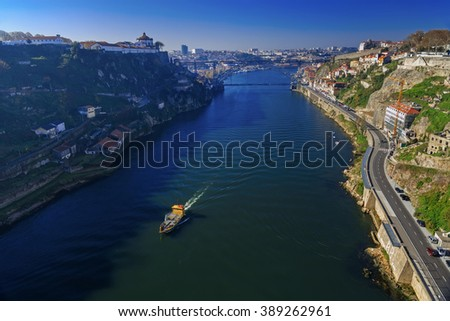 Luis I bridge and small ship sailing the river in Porto, Portugal, instagram toning