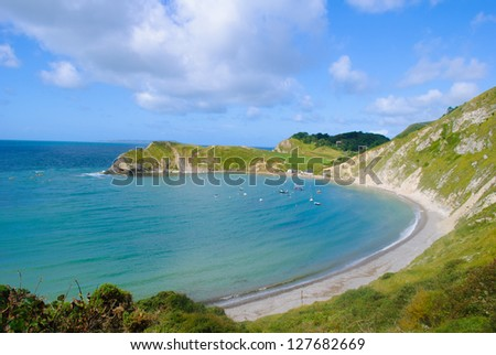 Lulworth Cove Bay Dorset with blue sky and sea - stock photo