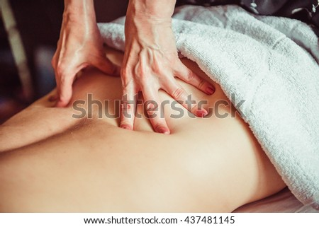 lumbar massage. Physiotherapist doing a massage technic on deep muscle. Lumbar. - stock photo