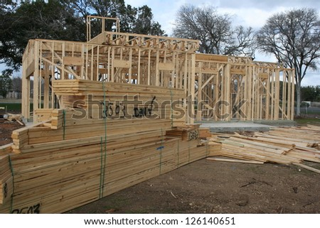 lumber and a new house - stock photo
