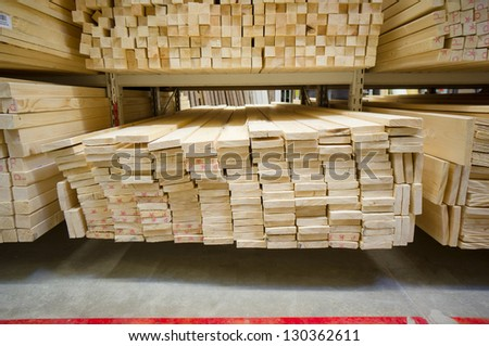 Lumber boards and beams of different sizes lie on racks and pallets in build supermarket