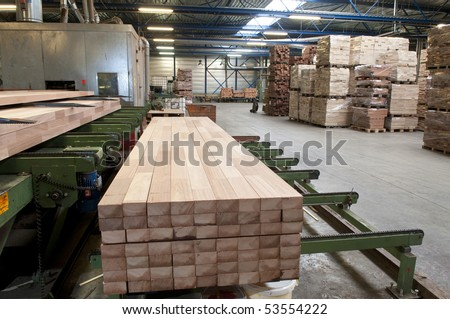 Lumber coming of the conveyer belt in a saw mill - stock photo
