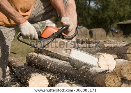 Lumberjack cutting the log of wood with petrol chainsaw - stock photo