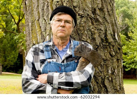lumberjack holding a double axe posing against a large tree - stock photo