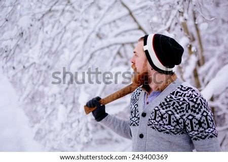 Lumberjack in the snowy winter forest. A man with a red beard and ax posing in a snowy winter forest.