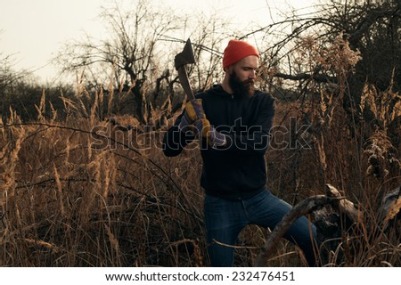 lumberjack is chopping stump in apple orchard - stock photo