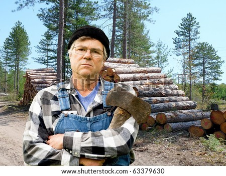 lumberjack portrait against a stack of freshly cut logs - stock photo