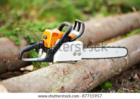 Lumberjack power Work tool petrol Chainsaw lying on log In The Forest - stock photo