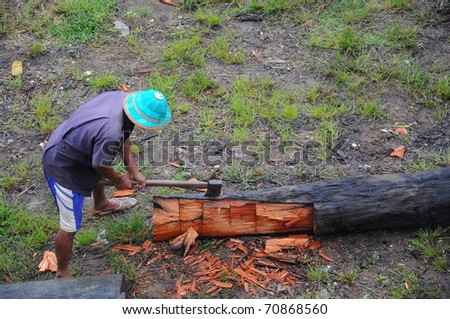 Lumberjack splitting wood with an axe - stock photo