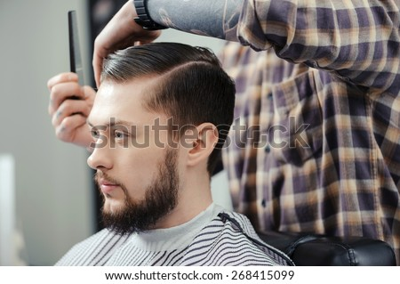 Lumberjack style. Male barber in plaid shirt combing hair of a male client at barbershop - stock photo