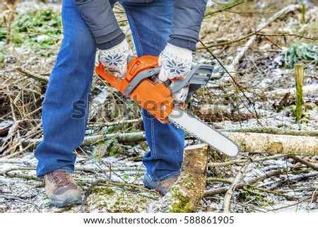 Lumberjack using chainsaw in forest