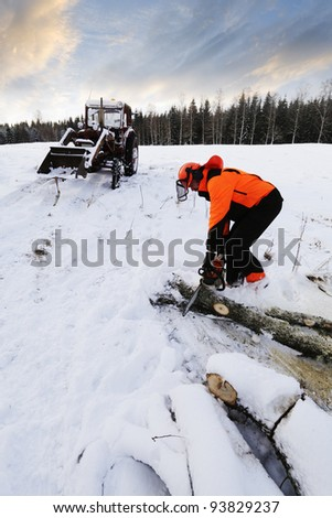 lumberjack with chainsaw in action, winter and snow - stock photo