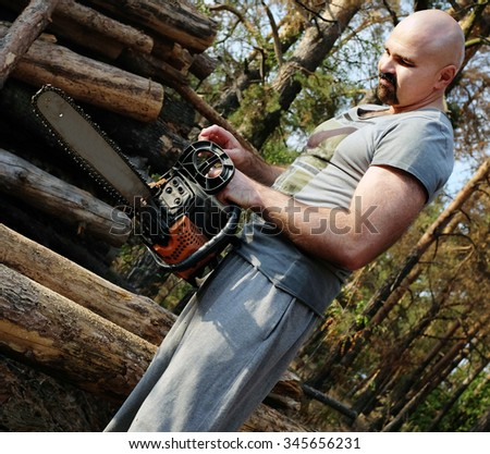 Lumberjack worker  cutting firewood in forest - stock photo