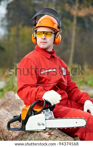 Lumberjack Worker in protective safety work wear With Chainsaw at Forest - stock photo