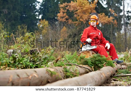 Lumberjack Worker With Chainsaw In The Forest. Resting - stock photo