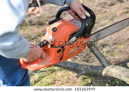 Lumberjack working with chainsaw, cutting wood. Selective focus