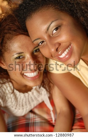 Luminous portrait of two happy women smiling while on a picnic outside; selective focus on the woman on the right. - stock photo