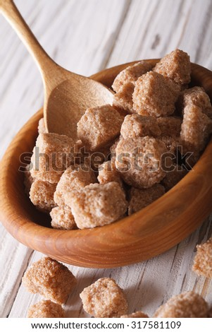 lump brown cane sugar macro in a wooden bowl on the table. Vertical