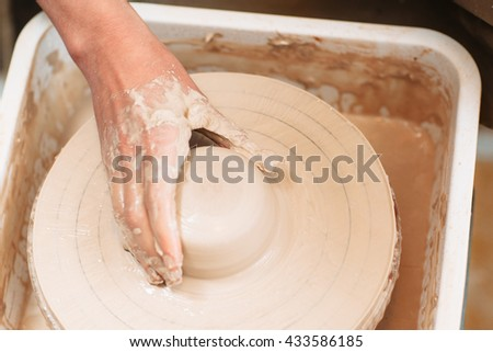 Lump of clay on spinning potters wheel with artisan hand. Top view on process of molding pottery. Close-up on potter hand on lump of clay on pottery wheel. - stock photo