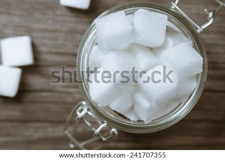 Lump sugar in glass jar - stock photo